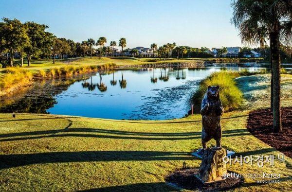"""PGA내셔널골프장 최대 승부처 15번홀에는 커다란 곰 동상과 함께 """"당신은 지금 베어트랩에 진입했다""""는 표지석까지 있다."""