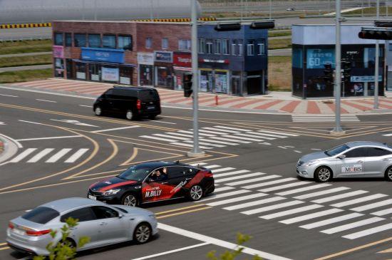 현대모비스 서산주행시험장 내 첨단시험로에서 자율주행 실험차량인 엠빌리의 실차 평가가 진행되고 있다. 교차로를 지나고 있는 엠빌리에 탑승한 연구원이 손을 흔들어 보이고 있다.