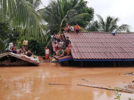 2018년 사고 당시 붕괴된 보조댐 인근 마을에서 주민들이 물에 잠긴 가옥의 지붕에 대피해 있는 모습. [이미지출처=연합뉴스]