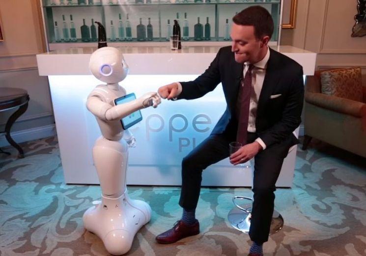 감정인식 인공지능(AI) 휴머노이드 '페퍼(Pepper)'가 TV프로그램에 나와 진행자와 주먹을 부딪히며 자신의 감정을 표현하고 있습니다. [사진=CNN 화면캡처]