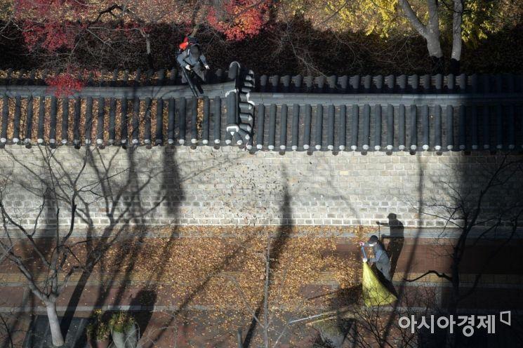 28일 덕수궁 관계자가 처마에 쌓인 낙엽을 청소하고 있다. /문호남 기자 munonam@