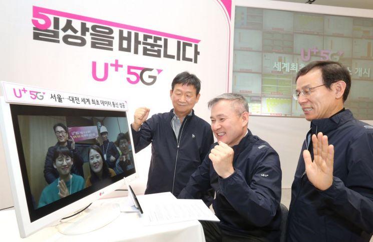 하현회 LG유플러스 부회장이 1일 5G 화상통화 중이다. 모니터와 하 부회장(중간) 사이에 위치한 검은색 폰이 삼성전자의 5G스마트폰 시제품이다.