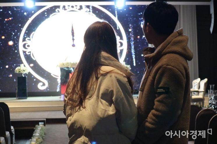 이호현·김소정씨 커플이 지난달 30일 텅 빈 예식장 주례석을 바라보고 있다. 둘은 지난해 하려던 결혼을 경제적 사정으로 두 차례나 미뤄야 했다.