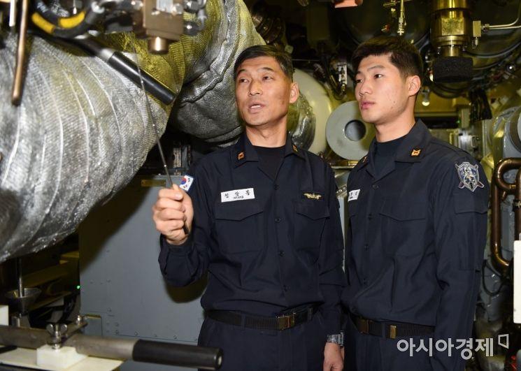 홍범도함 기관실에서 정상봉 준위(왼쪽)가 아들 정한민 하사에게 20여년간의 잠수함 생활로 쌓여진 업무 노하우를 알려주고 있다. (사진=해군 제공)