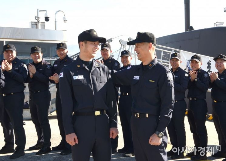 정한민 하사(왼쪽)의 전입을 홍범도함 승조원들이 환영하는 가운데 아버지 정상봉 준위가 아들을 격려하고 있다. (사진=해군 제공)
