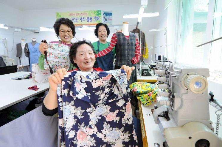 어르신들이 너나들이 공동작업장에서 옷 수선 작업을 하고 있다.