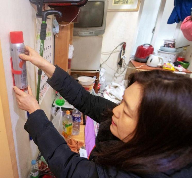 한 자원봉사자가 서울 용산구 동자동 쪽방촌을 다니며 간이소화용구를 부착하고 있다