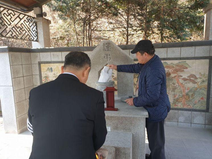 14일 낮 12시40분께 무연고 사망자들의 장례식이 모두 끝난 뒤, 서울시립승화원 유택동산에서 의전업체 직원들이 고(故) 무명 김경철씨의 분골을 산골함에 정성스레 붓고 있다. 사진=유병돈 기자