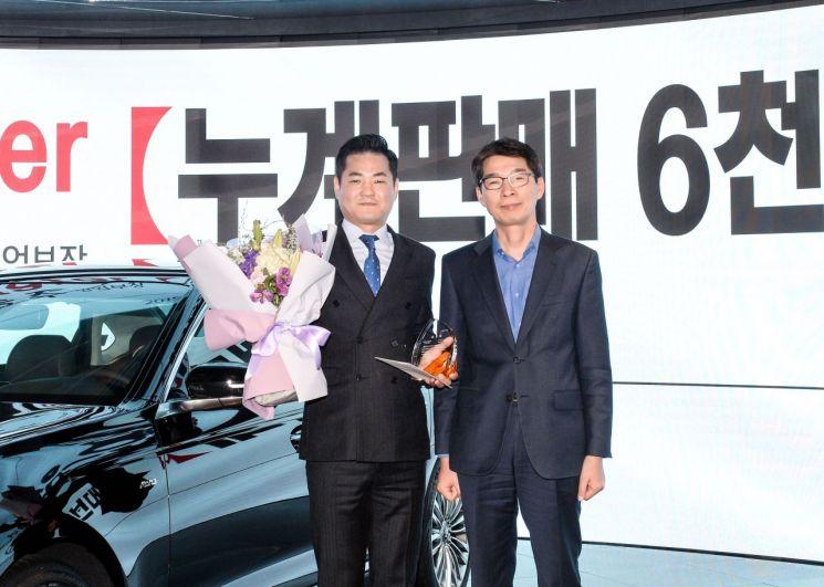 누계 판매 6000대를 돌파해 '그레이트 마스터'로 임명된 정송주 영업부장(왼쪽)과 기아차 국내영업본부장 권혁호 부사장(오른쪽)이 기념 사진을 찍고 있다.