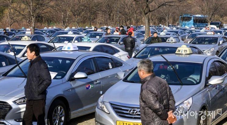 서울 택시 기본요금이 3000원에서 3800원으로 오른 18일 서울 마포구 난지천공원 주차장에 마련된 택시 미터기 작업 공간에서 택시운전수들이 미터기 조정을 받기 위해 기다리고 있다./강진형 기자aymsdream@