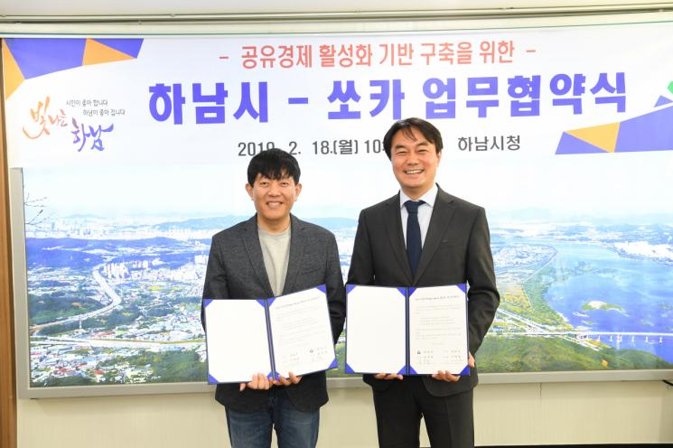 18일 이재웅 쏘카 대표(왼쪽)와 김상호 하남시장이 공유차량 활성화를 위한 업무협약(MOU) 체결식에서 협약서를 들고 기념사진을 찍다.