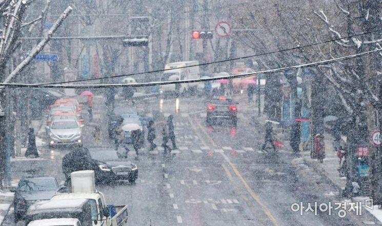 절기상 우수(雨水)이자 정월대보름인 19일 정부서울청사 인근에서 시민들이 눈을 맞으며 발걸음을 옮기고 있다. /문호남 기자 munonam@