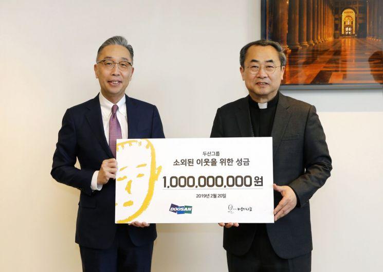 박지원 두산그룹 부회장(왼쪽)이 지난 20일 서울 명동성당에서 손희송 재단법인 바보의나눔 이사장에게 성금 10억 원을 전달했다.