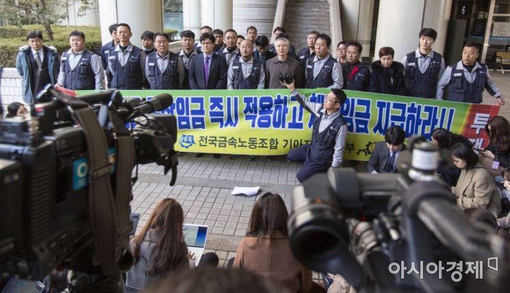 기아자동차 근로자들이 회사를 상대로 낸 통상임금 청구 소송 2심에서 일부 승소한 22일 서울 서초구 서울고등법원 서관 앞에서 기아자동차노조 관계자들이 입장발표를 하고 있다./강진형 기자aymsdream@