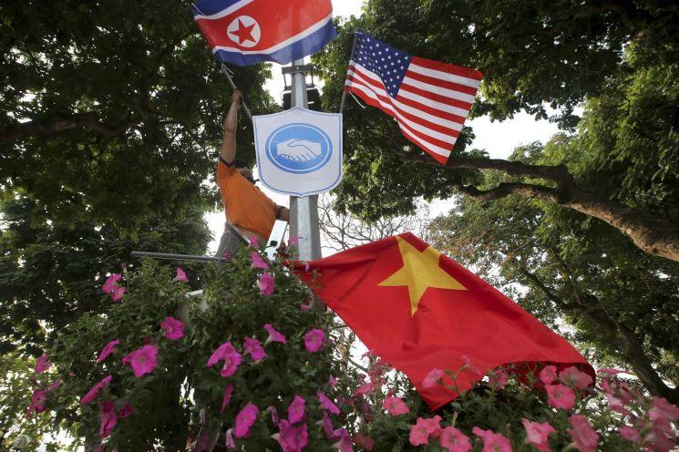 오는 27~28일 2차 북·미정상회담을 앞두고 21일(현지시간) 베트남 하노이 거리에서 한 작업자가 가로등 기둥에 성조기와 인공기 등을 걸고 있다. [이미지출처=연합뉴스]