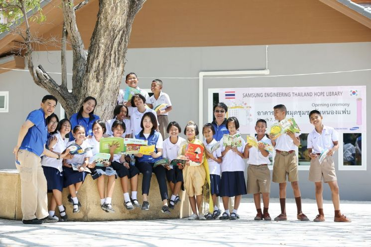 삼성엔지니어링 임직원과 태국 농팝마을 아이들이 태국 '희망도서관' 앞에서 기념촬영을 있다.