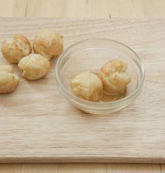 5. 다 튀긴 도넛은 튀김망이나 키친타월에 얹어 기름을 뺀다. 넓은 접시에 시럽을 담고 튀긴 도넛을 넣고 굴려 시럽을 묻힌 후 코코넛 슬라이스를 묻힌다.