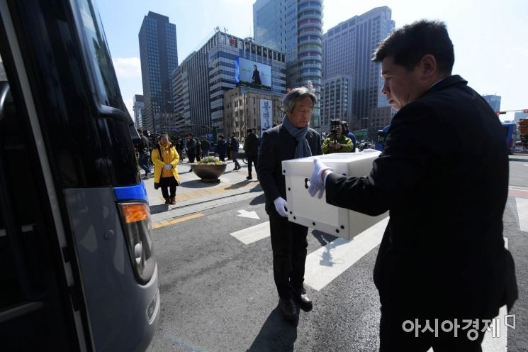 세월호 참사 희생자 및 미수습자 분향소에서 열린 이운식에서 관계자들이 희생자 영정이 담긴 상자를 버스에 싣고 있다. 뒤편 한 유족이 두 손을 모은 채 버스를 바라보고 있다. /문호남 기자 munonam@