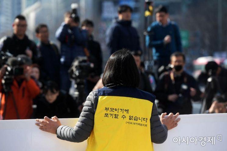세월호 천막이 철거되고 있는 가운데 참사 유족이 진상규명 및 책임자 처벌을 촉구하는 내용을 담은 대형 피켓을 들고 있다. 조끼에 적힌 '부모이기에 포기할 수 없습니다' 문구가 눈에 띈다. /문호남 기자 munonam@