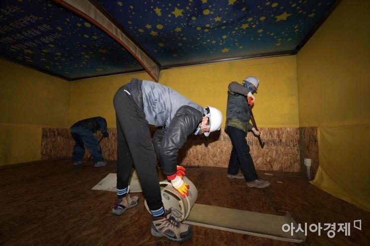세월호 분향소에서 서울시 관계자들이 장판과 벽지를 뜯어내고 있다. /문호남 기자 munonam@