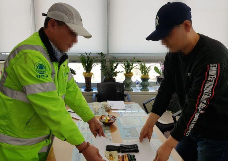 환경공무원 김모씨(왼쪽)이 황기호씨에게 물건을 전달하는 모습