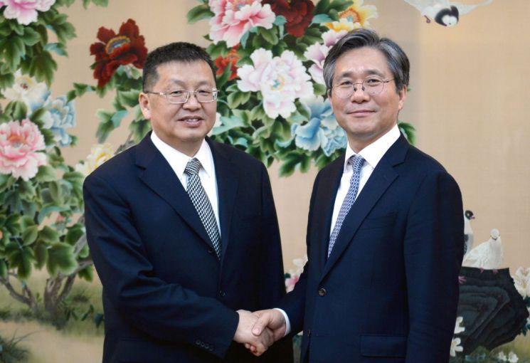 성윤모 산업통상자원부 장관(오른쪽)과 장젠화(章建?, Zhang Jianhua) 국가에너지국장(장관)이 악수를 하며 환하게 웃고 있다.