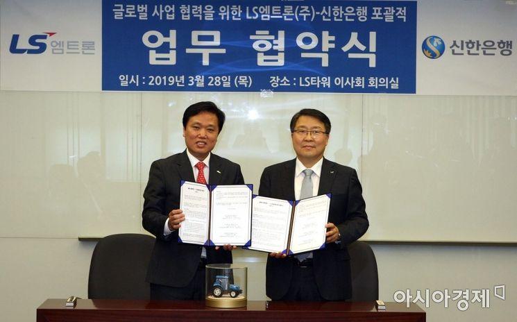 최동욱 신한은행 부행장(왼쪽)이 28일 LS타워에서 김연수 LS엠트론 대표와 글로벌 공동 마케팅을 위한 업무협약(MOU)을 체결하고 있다.