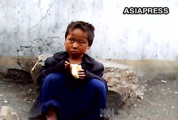 2011년 6월 평양의 한 거리에서 구걸한 빵을 먹고 있는 소년 노숙자(사진=아시아프레스).