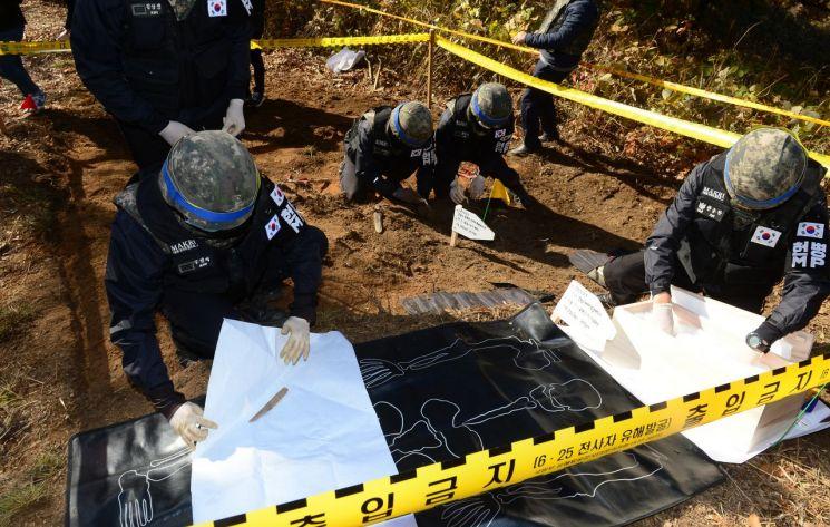 지난 2018년 10월 25일 강원도 철원군 백마고지 인근 화살머리고지에서 국방부 유해발굴감식단원들이 6.25 당시 전투에서 숨진 국군 유해를 발굴 뒤 수습하는 모습. <사진=공동취재단>