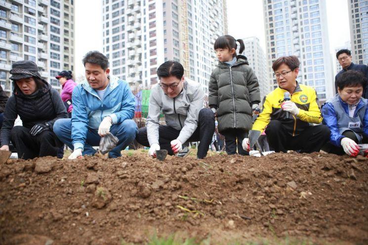 이정훈 강동구청장과 주민들이 명일근린공원 공동체텃밭에서 씨감자를 심고 있다.