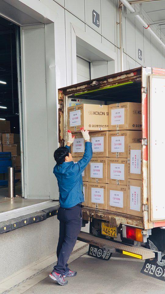 코오롱FnC 물류센터 직원들이 강원도 산불 피해지역에 전달할 구호물품을 트럭에 실는 모습.