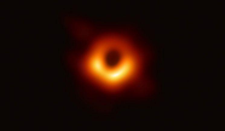 이번에 관측한 M87. 중심의 검은 부분은 블랙홀(사건의 지평선)과 블랙홀을 포함하는 그림자이고, 고리의 빛나는 부분은 블랙홀의 중력에 의해 휘어진 빛이다. 관측자로 향하는 부분이 더 밝게 보인다.