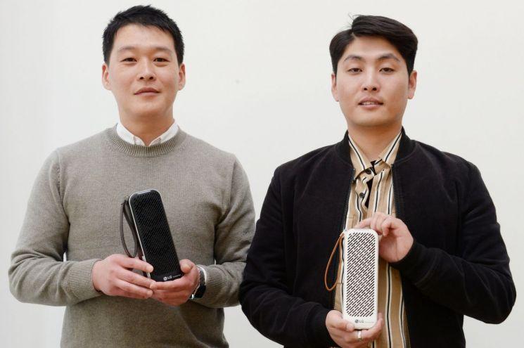 전종건 LG전자 홈어플라이언스&에어솔루션(H&A) 상품기획담당 책임(왼쪽)과 구명진 LG전자 에어솔루션연구소 선임연구원이 휴대용 공기청정기 '퓨리케어 미니'를 들고 포즈를 취하고 있다.