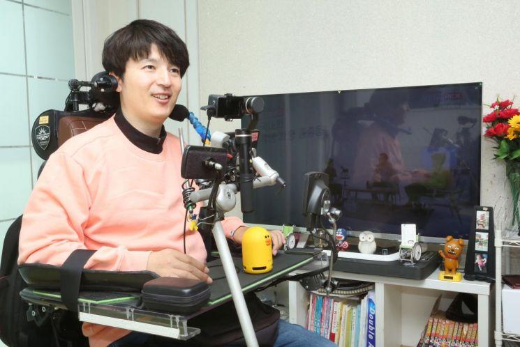 척수장애인 이원준 씨가 'U+우리집AI' 서비스를 이용해 음성명령으로 장애인 콜택시를 호출하고 있다.