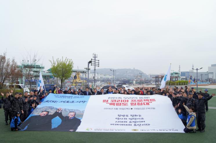 18일 백령도원정대 출정식에서 4.27남북정상회담 1주년 기념 현수막을 펼치고 참석자들이 평화통일을 연호하고 있다. (사진=탈북민사랑나눔운동본부)