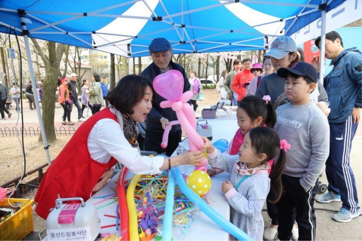 개화산 봄꽃 축제에 참여한 어린이가 아트풍선 만들기를 체험하고 있다.