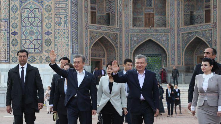 우즈베키스탄을 국빈방문 중인 문재인 대통령이 샤프카트 미르지요예프 대통령과 20일 오후 (현지시간) 사마르칸트 레기스탄 광장에서 박수치는 시민들에게 손을 흔들고 있다. [이미지출처=연합뉴스]