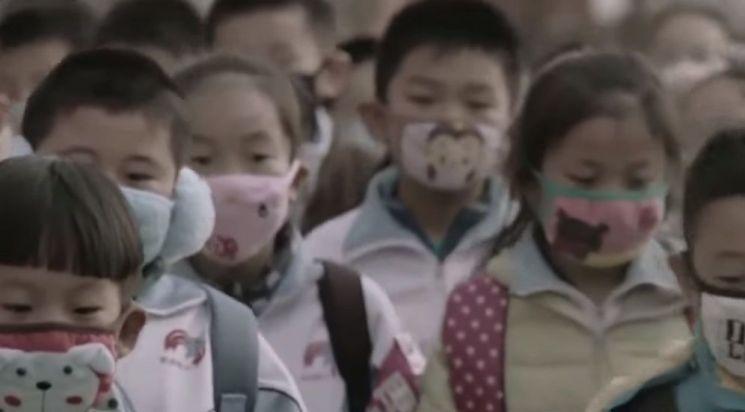 대기오염이 극심한 도로변을 걸어 등교하는 어린이들의 모습. [사진=유튜브 화면캡처]