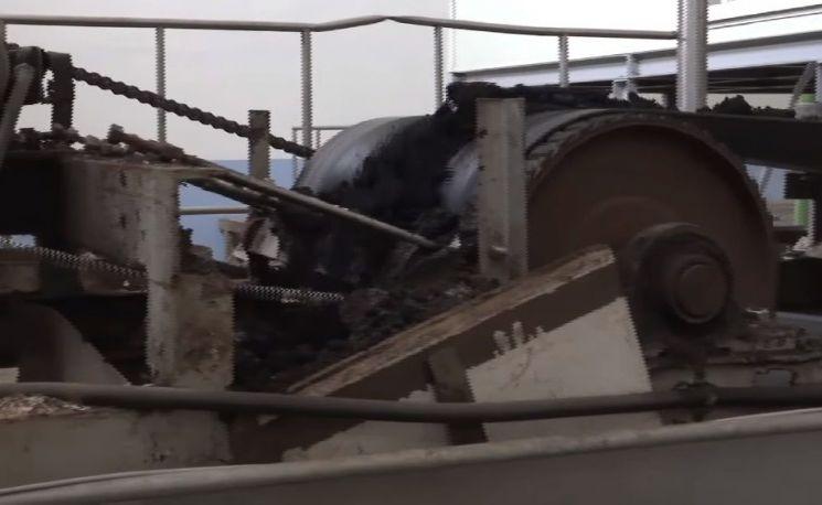 오염된 물을 처리하고 남은 찐득한 찌꺼기인 폐기물 덩어리가 컨베이어밸트 위를 순환하며 건조되는 모습. [사진=유튜브 화면캡처]