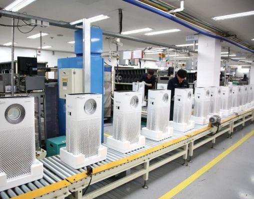 웅진코웨이 유구공장 직원들이 공기청정기 생산라인에서 제품들을 살펴보고 있다.
