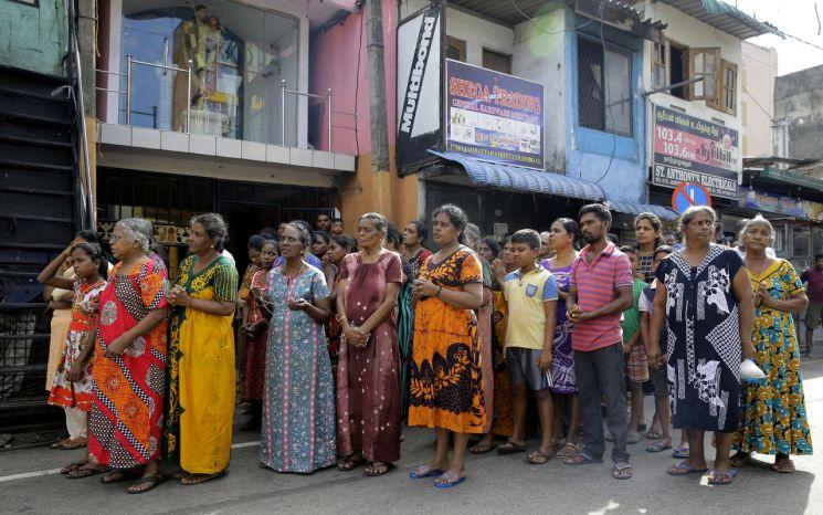 부활절인 지난 21일(이하 현지시간) 발생한 연쇄 폭발 테러가 발생한 스리랑카 콜롬보 시내 성 안토니오 성당 인근에서 23일 시민들이 희생자들을 애도하는 '3분간의 묵념'에 참여하고 있다. [이미지출처=연합뉴스]