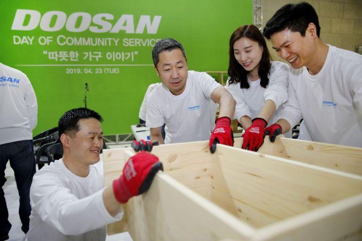 박정원 두산그룹 회장(가운데)이 임직원들과 함께 인근 지역 가정에 전달할 가구를 제작하고 있다.