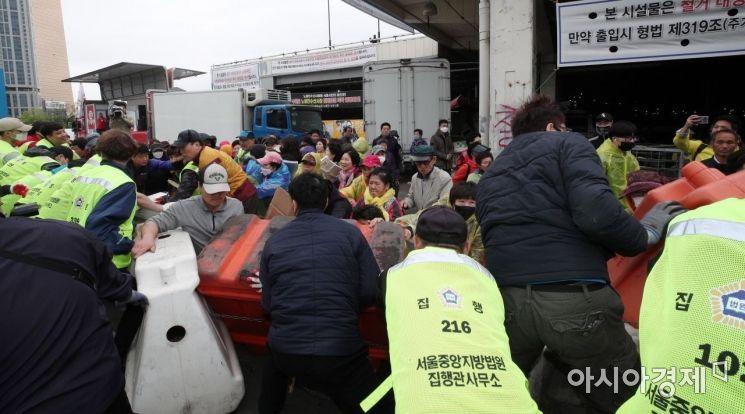 옛 노량진수산시장의 다섯 번째 명도소송강제집행이 실시된 25일 서울 동작구 노량진수산시장에서 구시장 상인들이 집행관들의 집행을 저지하고 하고 있다. 수협은 지난 2017년 4월부터 네 차례에 걸쳐 명도집행을 시도했으나 상인들의 강경 대응에 막혀 번번이 무산됐다./김현민 기자 kimhyun81@