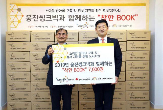 이재진 웅진씽크빅 대표(오른쪽)와 천진욱 한국백혈병소아암협회 사무총장이 도서 선물세트 전달식에서 기념촬영을 하고 있다.