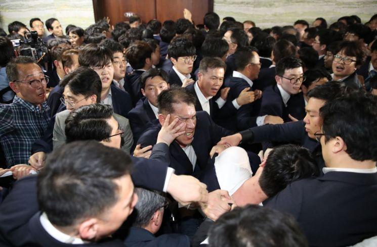 자유한국당 의원과 보좌관들이 지난달 25일 국회 의안과 진입을 시도하다 국회 관계자들과 몸싸움을 벌이고 있다. [이미지출처=연합뉴스]