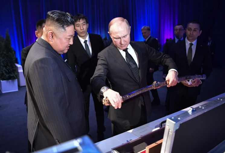 김정은 북한 국무위원장(왼쪽)과 블라디미르 푸틴 러시아 대통령(가운데)이 25일 러시아 블라디보스토크 루스키 섬의 극동연방대학에서 정상회담을 마친 후 검을 선물로 주고받고 있다.  <사진=AFP연합>