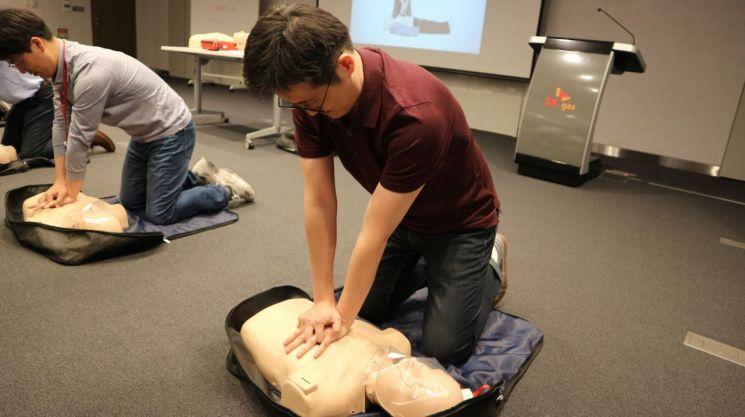 ▲SK가스는 26일 임직원 20명이 한국응급처치교육원이 제공하는 심폐소생술 교육을 4시간 동안 받았다. 사진은 SK가스 임직원이 응급구조 실습에 임하고 있는 모습.