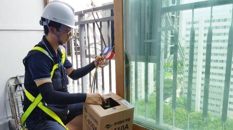 삼성전자서비스 수리 엔지니어가 가정 내 설치된 에어컨 실외기를 점검하고 있다. /사진제공=삼성전자서비스.