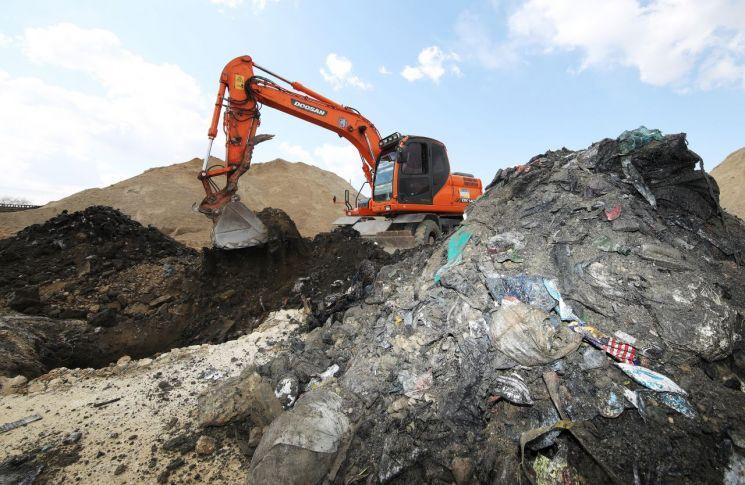지난달 13일 경기도의 한 골재 매매업소에서 굴삭기가 땅속에 묻혀있던 쓰레기를 퍼 올리고 있는 모습. 기사 내용은 사진과 무관함.  <사진=연합뉴스>