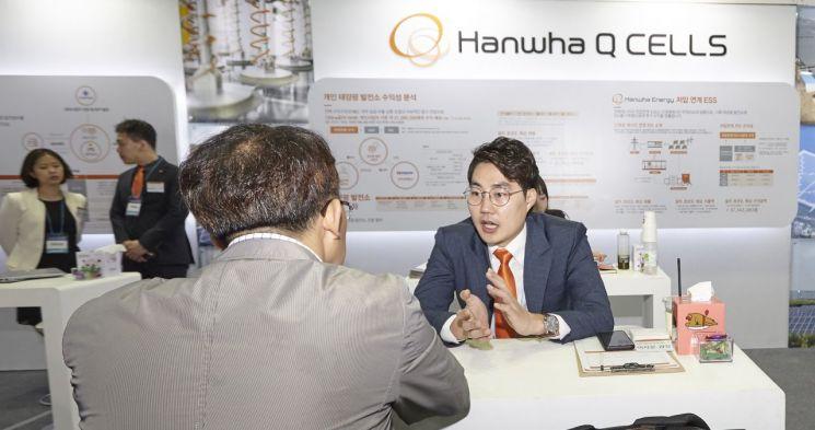 ▲한화큐셀 직원이 서울 머니쇼 한화큐셀 부스(2018)에서 개인용 태양광 발전소 관련 상담을 진행하고 있다.